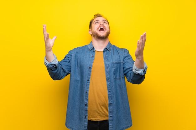 Homem loiro sobre parede amarela isolada gritando para a frente com a boca aberta