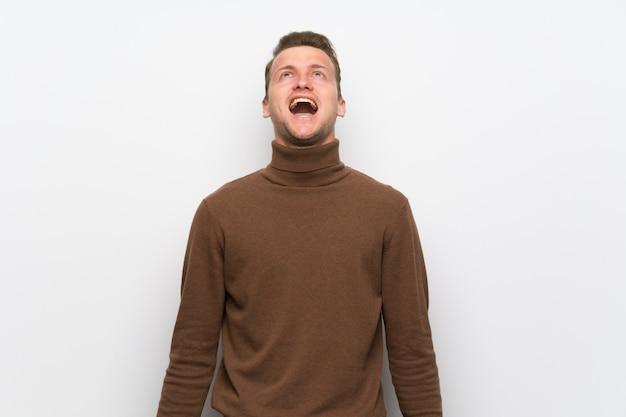 Homem loiro sobre parede branca isolada, gritando para a frente com a boca aberta