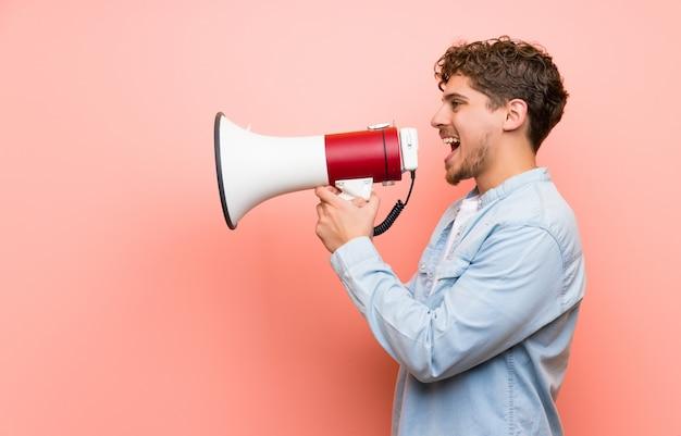 Homem loiro sobre parede rosa gritando através de um megafone