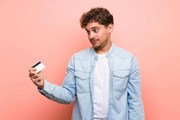 Homem loiro sobre parede rosa, tendo um cartão de crédito sem dinheiro