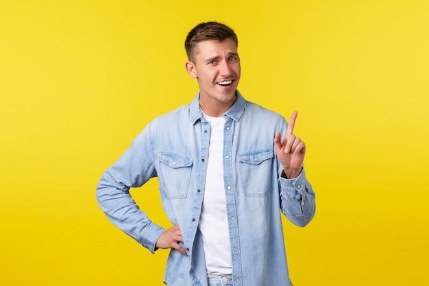 Homem loiro sorridente e alegre sacudindo o dedo, diga não tão rápido, repreendendo alguém ou pedindo espere, espere um segundo, em pé fundo amarelo otimista, mostrando um anúncio no topo