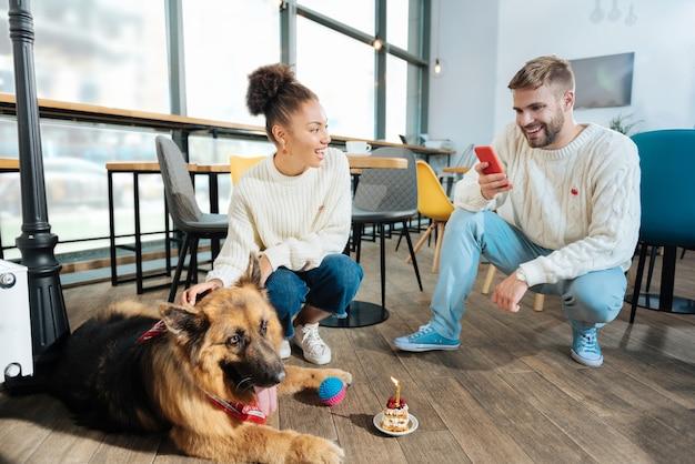 Homem loiro sorridente fazendo foto de seu cachorro grande e fofo enquanto brincava com ele no café