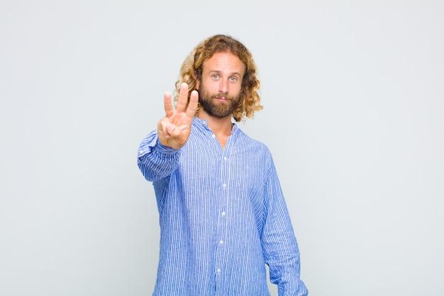 Homem loiro sorrindo e parecendo amigável, mostrando o número três ou terceiro com a mão para a frente, em contagem regressiva