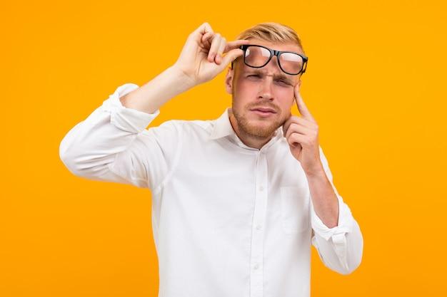 Homem loiro vestido com uma camisa branca clássica estrabismo ao tirar os óculos no amarelo