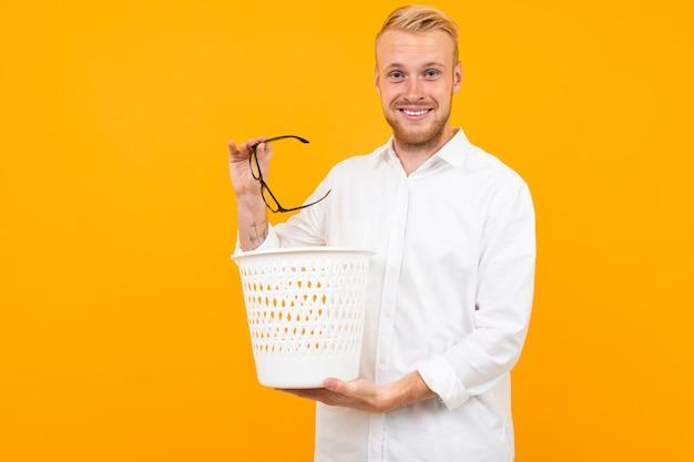Homem loiro, vestido com uma camisa branca clássica lança óculos na lixeira onyellow