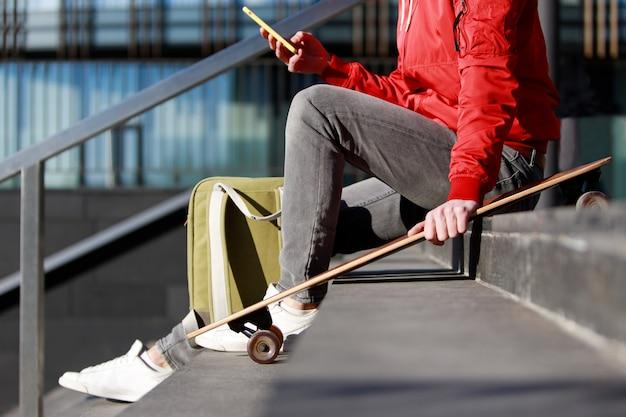 Homem longboarder em roupas casuais, usando seu smartphone, descansando nos degraus, sentado com longboard / skate ao ar livre