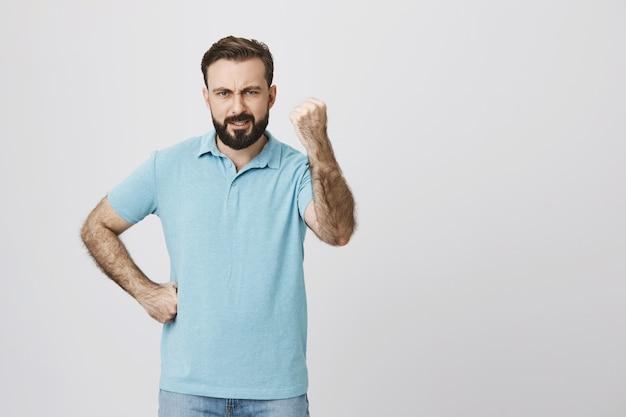 Homem louco e desapontado balançando o punho com raiva, repreendendo