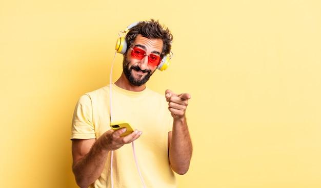 Homem louco expressivo apontando para a câmera e escolhendo você com fones de ouvido