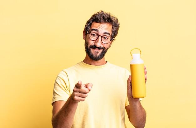 Homem louco expressivo apontando para a câmera escolhendo você com uma garrafa térmica de chá