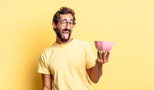 Homem louco expressivo com atitude alegre e rebelde, brincando e mostrando a língua e segurando uma panela