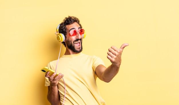 Homem louco expressivo com orgulho, sorrindo positivamente com o polegar para cima com fones de ouvido
