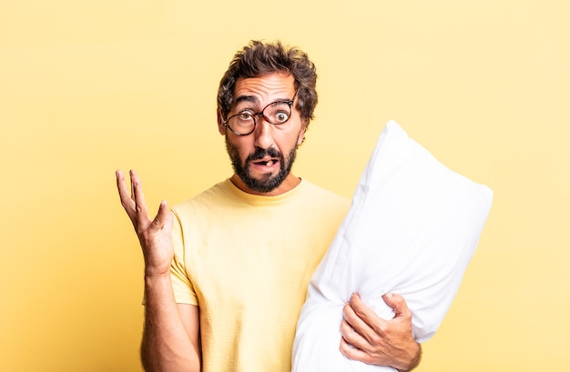 Homem louco expressivo gritando com as mãos para o alto e segurando um travesseiro
