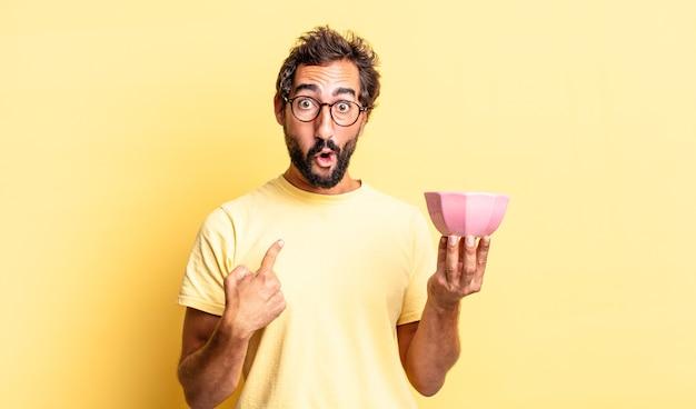 Homem louco expressivo parecendo chocado e surpreso com a boca bem aberta, apontando para si mesmo e segurando uma panela