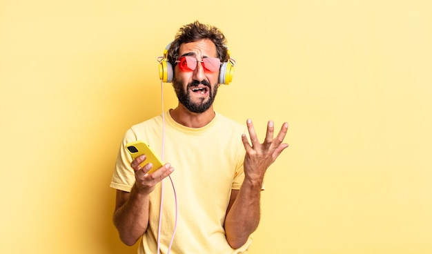 Homem louco expressivo parecendo desesperado, frustrado e estressado com fones de ouvido