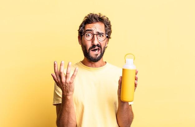 Homem louco expressivo parecendo desesperado, frustrado e estressado com uma garrafa térmica de chá