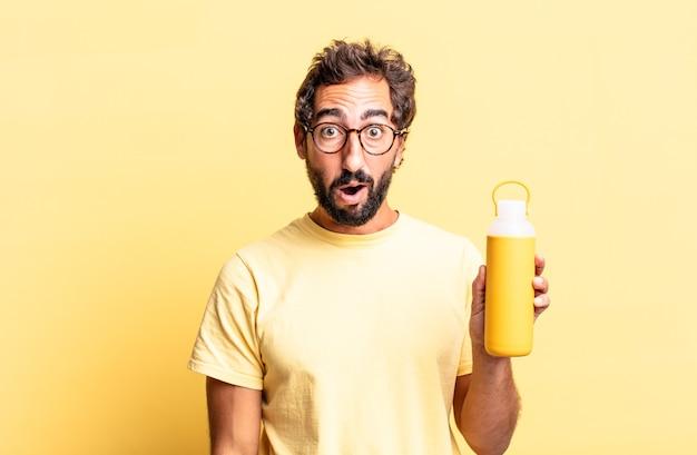 Homem louco expressivo parecendo muito chocado ou surpreso com uma garrafa térmica de chá