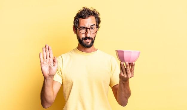 Homem louco expressivo parecendo sério mostrando a palma da mão aberta fazendo gesto de pare e segurando um pote