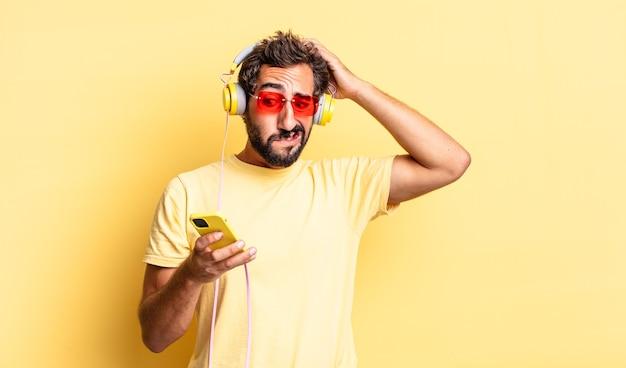 Homem louco expressivo se sentindo estressado, ansioso ou com medo, com as mãos na cabeça e fones de ouvido