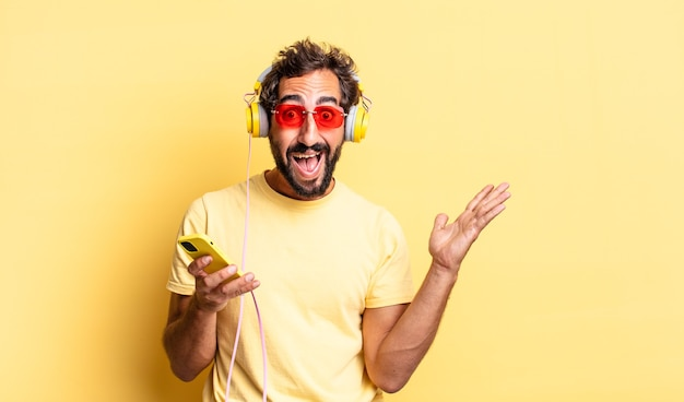 Homem louco expressivo se sentindo feliz e surpreso com algo inacreditável com fones de ouvido