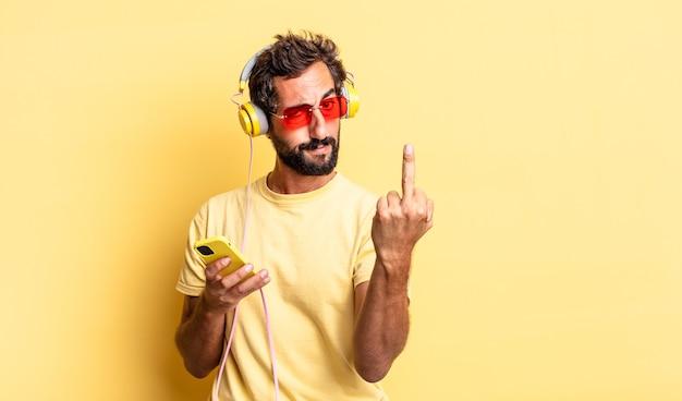 Homem louco expressivo se sentindo irritado, irritado, rebelde e agressivo com fones de ouvido