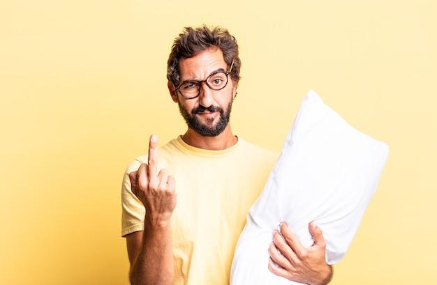Homem louco expressivo se sentindo irritado, irritado, rebelde e agressivo e segurando um travesseiro