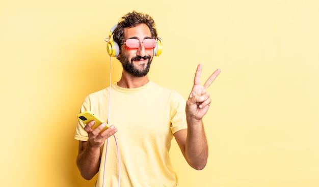 Homem louco expressivo sorrindo e parecendo amigável, mostrando o número dois com fones de ouvido