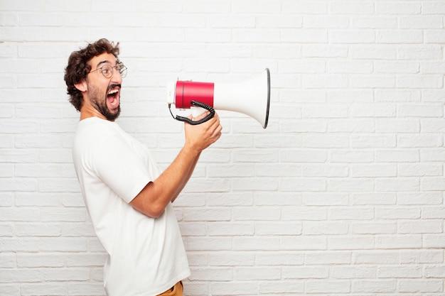 Homem louco novo com um megafone contra a parede de tijolo.