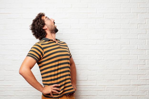 Homem louco ou bobo jovem gesticulando e expressando emoções contra o fundo da parede de tijolo