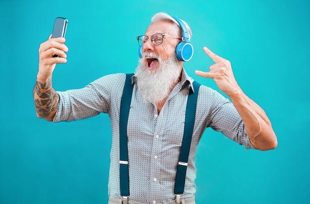 Homem louco sênior usando o aplicativo de smartphone para criar lista de reprodução com música rock