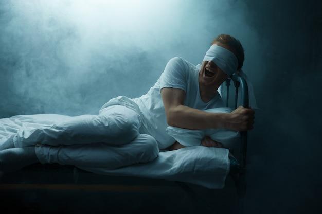 Homem louco vendado sentado na cama, quarto escuro .. homem psicodélico tendo problemas todas as noites, depressão e estresse, tristeza, hospital psiquiátrico