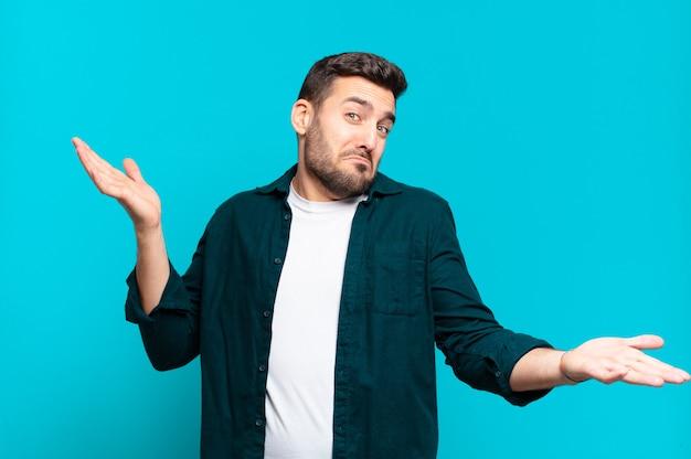 Homem louro adulto bonito encolhendo os ombros com uma expressão estúpida, maluca, confusa e perplexa, sentindo-se irritado e sem noção