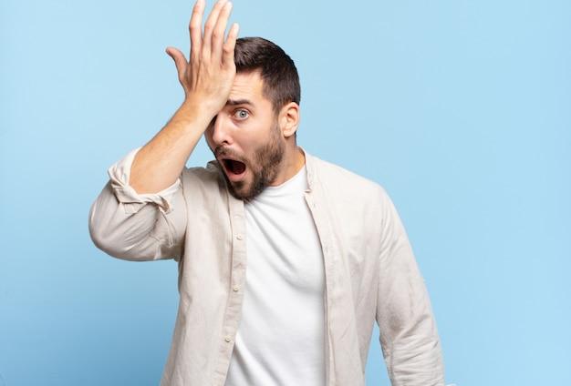 Homem louro adulto bonito erguendo a palma da mão na testa pensando, opa, depois de cometer um erro estúpido ou lembrar, sentir-se bobo