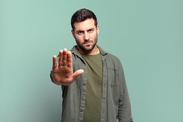 Homem louro adulto bonito parecendo sério, severo, descontente e irritado, mostrando a palma da mão aberta fazendo gesto de pare