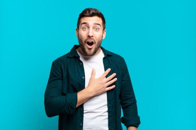 Homem louro adulto bonito se sentindo chocado e surpreso, sorrindo, levando a mão ao coração, feliz por ser o único ou mostrando gratidão