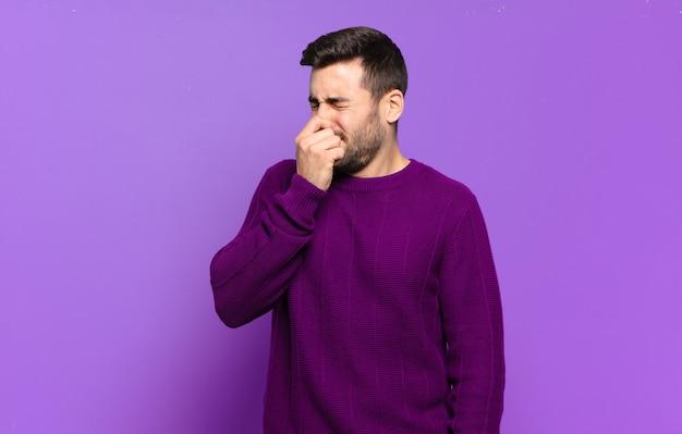 Homem louro adulto bonito se sentindo enojado, segurando o nariz para evitar cheirar um fedor desagradável e desagradável