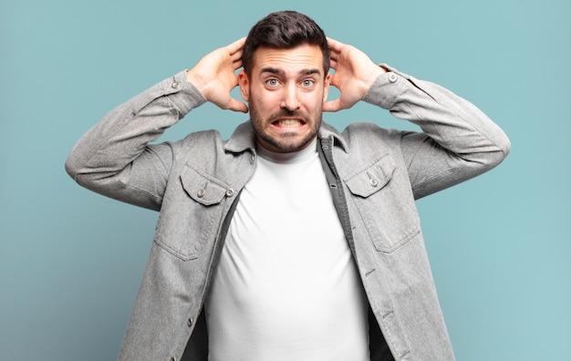 Homem louro adulto bonito se sentindo estressado, preocupado, ansioso ou com medo, com as mãos na cabeça, entrando em pânico com o erro