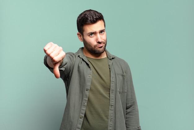 Homem louro adulto bonito se sentindo zangado, irritado, chateado, desapontado ou insatisfeito, mostrando o polegar para baixo com um olhar sério