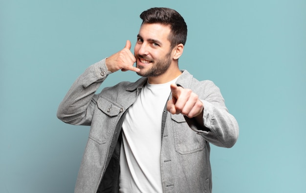 Homem louro adulto bonito sorrindo alegremente e apontando para a frente enquanto faz um gesto depois de ligar para você, falando ao telefone
