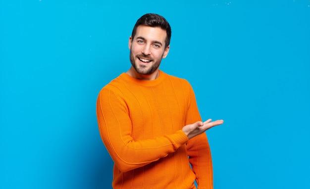 Homem louro adulto bonito sorrindo alegremente, se sentindo feliz e mostrando um conceito no espaço da cópia com a palma da mão