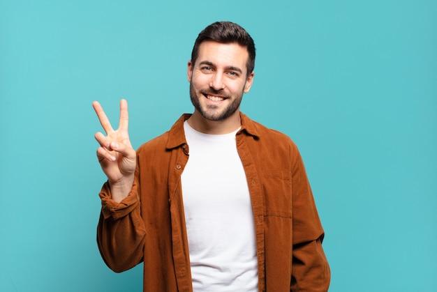 Homem louro adulto bonito sorrindo e parecendo amigável, mostrando o número dois ou o segundo com a mão para a frente, em contagem regressiva