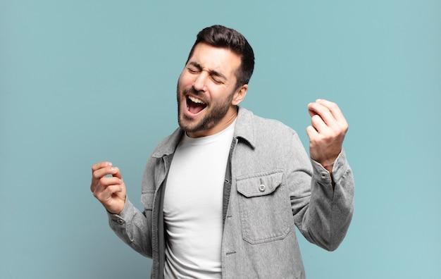 Homem louro adulto bonito sorrindo, sentindo-se despreocupado, relaxado e feliz, dançando e ouvindo música, se divertindo em uma festa