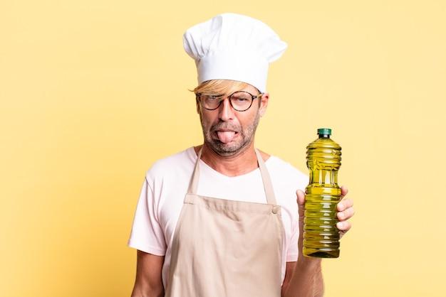 Homem louro bonito chef adulto segurando uma garrafa de azeite