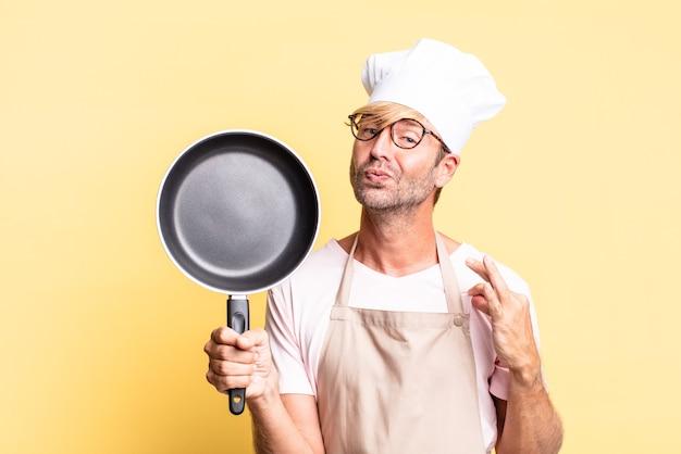 Homem louro e bonito chef adulto segurando uma panela