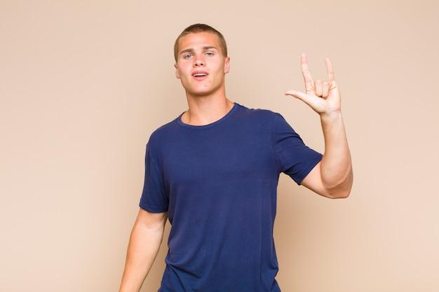 Homem louro se sentindo feliz, divertido, confiante, positivo e rebelde, fazendo sinal de rock ou heavy metal com a mão