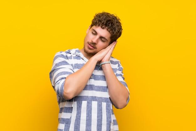 Homem louro sobre a parede amarela que faz o gesto do sono na expressão dorable