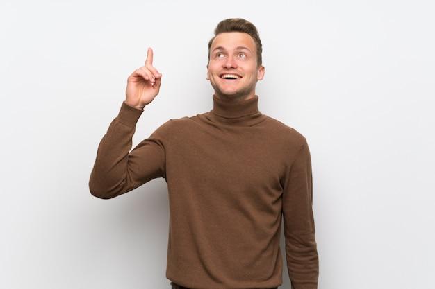 Homem louro sobre a parede branca isolada que pretende realizar a solução ao levantar um dedo