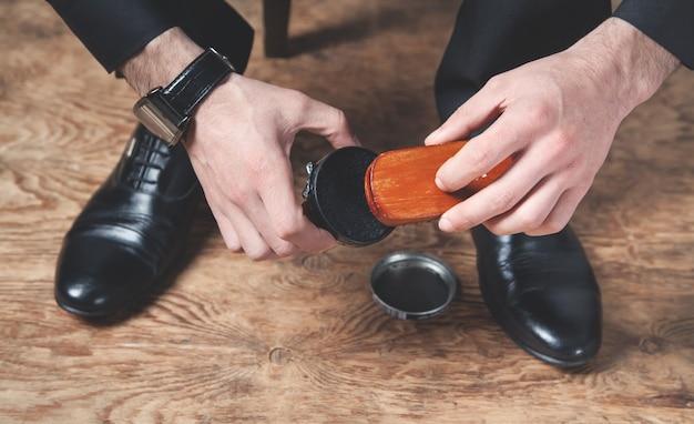 Homem lustrando sapatos com um pincel.