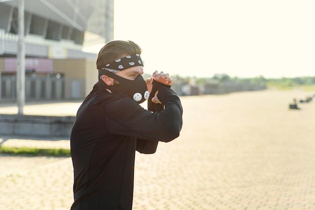 Homem lutador treinando boxe soco na rua urbana retrato de homem fitness boxe ao ar livre no preto
