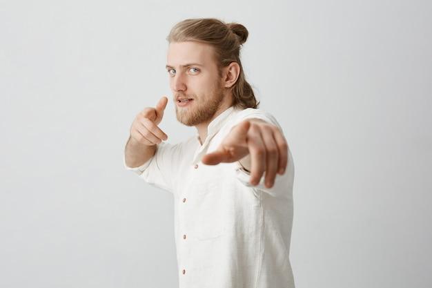 Homem macho confiante com cabelos loiros e coque, apontando para a câmera com os dedos indicadores