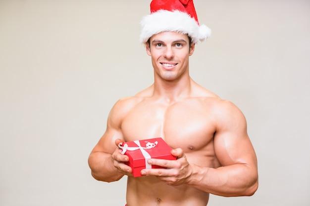 Homem macho sem camisa em presente de presente de chapéu de santa
